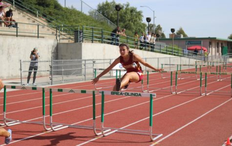 Junior, Jacqueline Chavez jumping over a hurdle during the race.