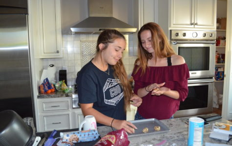 Madison Augusto (12) and Savannah Pierce (12) bake cookies in order to assemble yummy 'Dracula's Dentures' treats