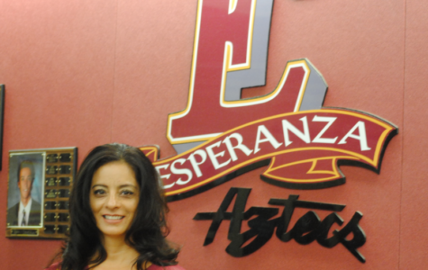 Mrs. Kettering representing Esperanza Aztecs in front of the sign.