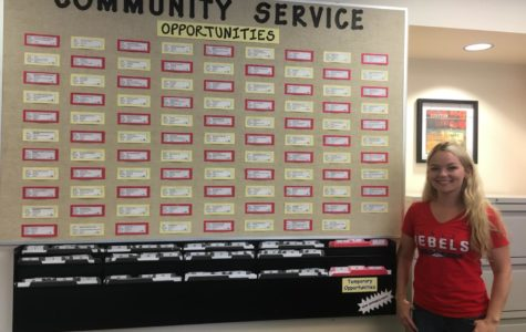 Cheyenne Beever posing next to the Community Service wall.