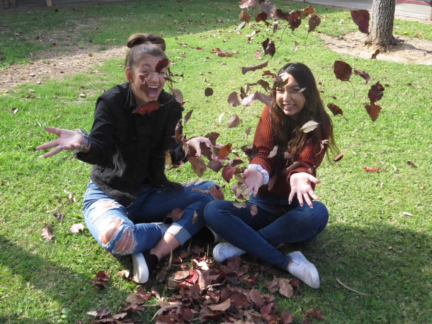 Chloe Masciale and Laila Najem playing around with the fall leaves as they get ready for Thanksgiving break.