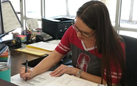 Registrar Amy Austin working over a student transcript at her desk.