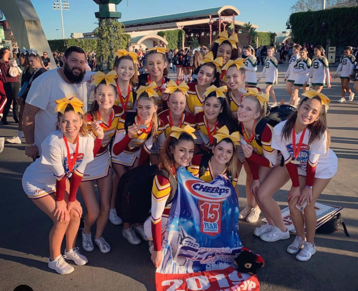 Cheer squad after competition celebrating their first place win with their banner.