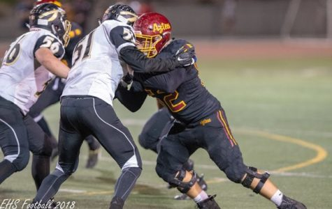 Varsity player Calvin Flores (junior) tackles an opposing player in the last season.