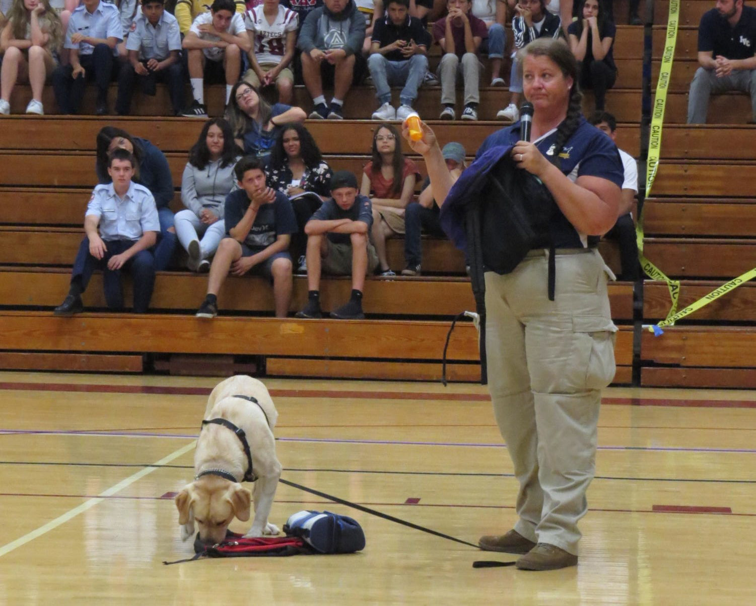 Tonya Anderson, with the help of Mia the yellow lab, find medications in an example backpack at the Drug Dog Assembly.